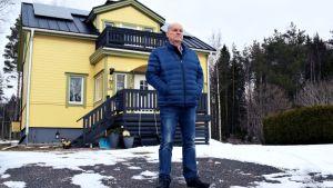 Birger Ekman står framför sitt gula hus i lite smått vinterväder.