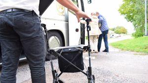 En äldre kvinna får hjälp ombord på en buss medan en annan person lyfter in hennes rollator i bussens bagageutrymme.