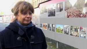 En kvinna till vänster, till höger informativa planscher om Berlinmurens fall.