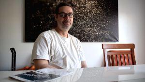 Peter Flinkman sitter vid ett bord, iklädd vid t-shirt.