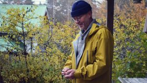 Kristian Lindroos med några nycklar i sin hand. Han har en gul rock på sig i ett gult och grannt höstlandskap.