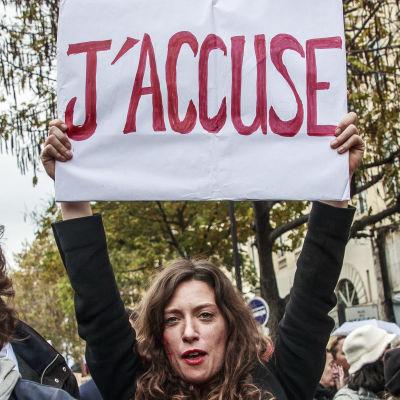 Kvinna håller upp skylt där det står ''Jag anklagar'' under demonstration mot närståendevåld i Paris.