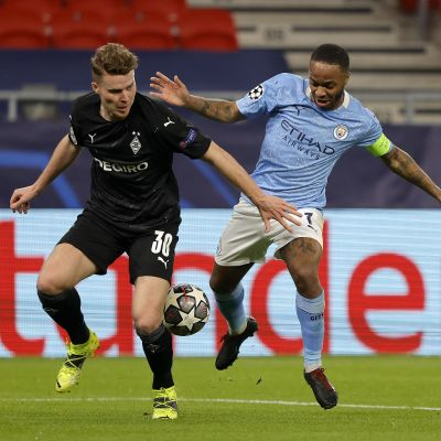 Manchester Cityn Raheem Sterling kamppailee pallosta M'gladbachin Nico Elvedin kanssa.