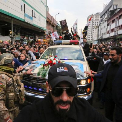 Folk går i en procession, i mitten en bil med de döda.