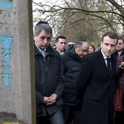 Emmanuel Macron bredvid en judisk grav som någon målat ett hakkors på.