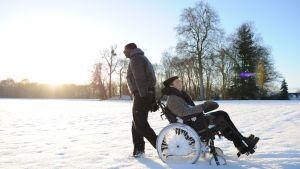 Driss (Omar Sy) vetää Philippen (François Cluzet) pyörätuolia lumessa