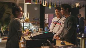 Ung kvinna står bakom kafédisk och två kunder gör en beställning.