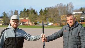 Hannu Sääskilahti i grå tröija och keps håller i ett bobollsträ tillsammans med Matti Pelander i grå jacka.