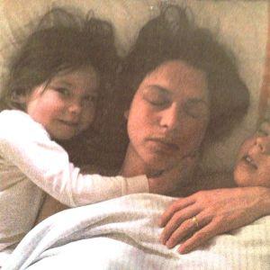 Pikku tyttö, äiti ja poika lepäävät sängyssä. Äiti nukkuu