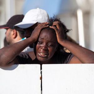 En kvinna gråter ombord på ett av den italienska kustbevakningens räddningsfartyg.