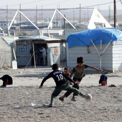 Lapsia pelaamassa jalkapalloa pakolaisleirillä.