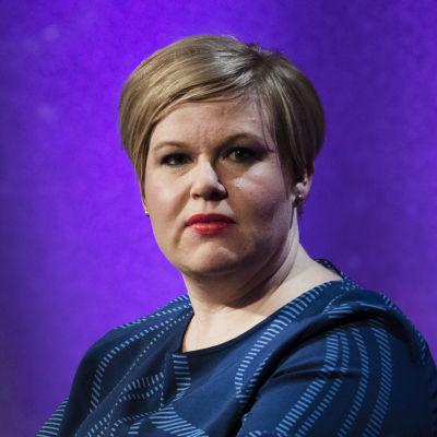 Annika Saarikko, klädd i klarblått, sitter med händerna knäppta framför sig.