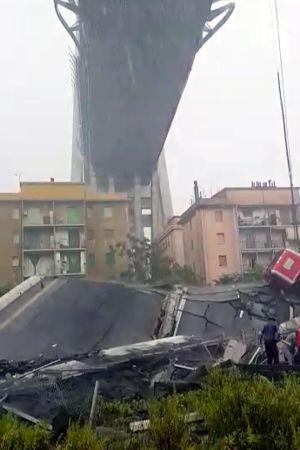 En bit av den raserade bron ligger på marken framför några hus