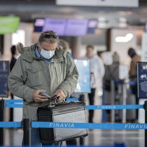 Passagerare med munskydd och liten kappsäck på Helsingfors-Vanda flygplats.