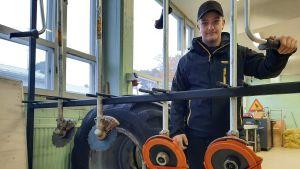 Jonas Westerholm står i en hall med en röjsåg.