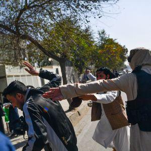 Två beväpnade män slår till en annan man bakifrån på en gata.