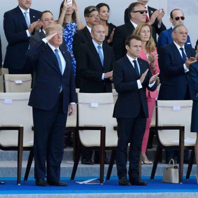 Presidentit Donald Trump ja Emmanuel Macron puolisoineen seuraamassa sotilasparaatia.