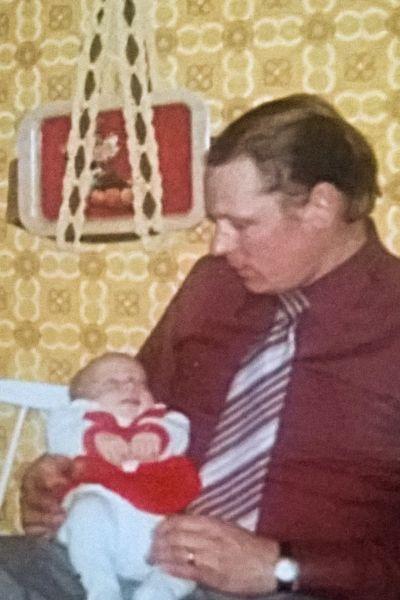 Anna som baby ligger i sin pappas famn.