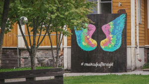Trähusmiljö, innergård med lövträd, skylt med en fjäril målad på samt texten #musikcafeaftereight