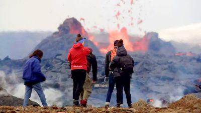 Några personer står med ryggen mot kameran och tittar på glödande lava som sprutar upp.