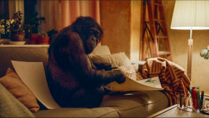 Apina istuu sohvalla. Ruutukaappaus elokuvasta The Square (2017)..