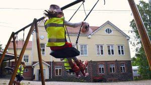 Ett förskolebarn gungar i hård fart på gården till Dalsbruk skola.