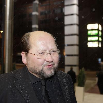 Mitro Repo står i snöfall i svart kostym.