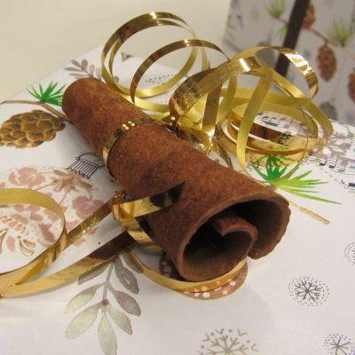 Kuvassa joululahjapaketti, jossa koristeena kanelitanko.