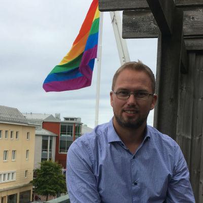En man med skägg och glasögon iklädd blå skjorta sitter på en balkong med en prideflagga i bakgrunden.