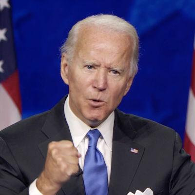 Joe Biden håller tal med usa:s flaggor i bakgrunden.