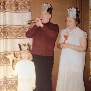 Pikkutyttö ja isovanhemmat yhteisessä esiintymisleikissä, kaikilla kultapahviset kruunut päässä.