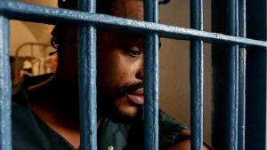 Mies nojaa päätänsä vankilan kaltereihin