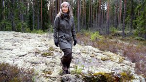 Anneli Jussila går på en bergsknall i skogen.