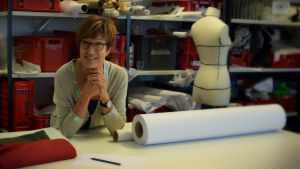 Marjut Yli-Mäyry lutar sig med armbågarna mot ett bord, i bakgrunden en provdocka, rullar med tyg och plastbackar.