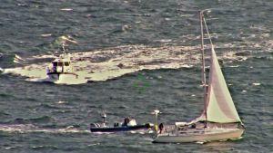 En segelbåt till höger och två motorbåtar till vänster.