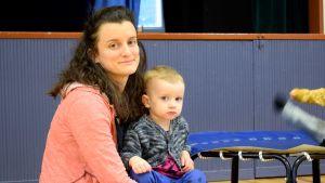 Amy Lindroos sitter på golvet med sin 3-åriga dotter i famnen.