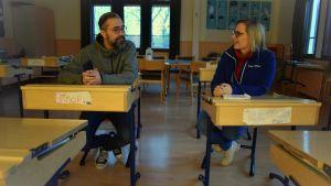 Sabina Simola-Ström och Micke Gunnarsson sitter i var sin pulpet i ett klassrum och pratar med varandra.