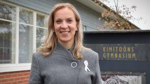 Sandra Bergqvist iklädd en grå rock står framför kimitoöns gymnasieskola, en låg, röd teglbyggnad.