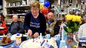 Runa Heino skär upp tårta i bybutiken Knallis.