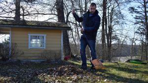 Mikko Pihlström krattar gården en solig vårmorgon.
