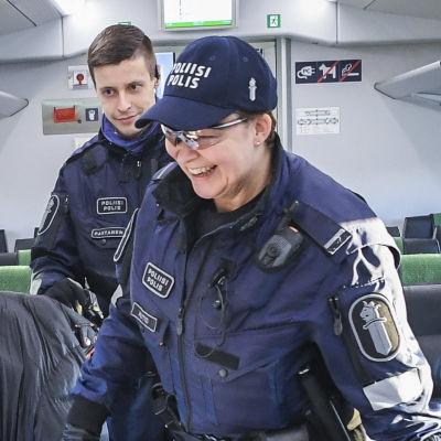 En polis kontrollerar en tågresenärs person- och reseuppgifter under coronavåren då Nyland var stängt.