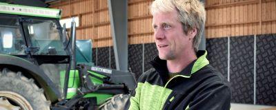 Claus Blomberg står i en lagerhall framför en grön traktor.