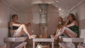 Kolme saunojaa istuu saunassa, jossa seinälle heijastuu ulkona oleva maisema väärinpäin.