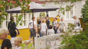 Ihmisiä vanhan keltaisen puutalon terassilla.