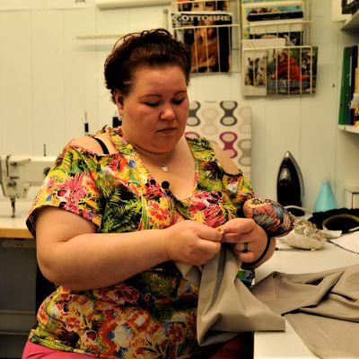 Företagaren Erica Wickman gör ändringsarbeten i sin kombinerade syateljé och klädbutik