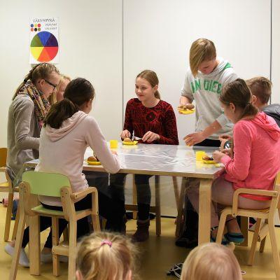 Kuvassa yläkoululaisia ruokapöydän ääressä.