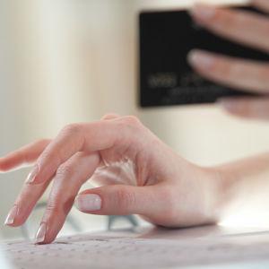 En person håller upp ett bankkort och knappar samtidigt på ett tangentbord.