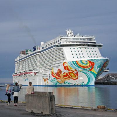 Stort kryssningsfartyg i hamn, tre kvinnor står och tittar på.