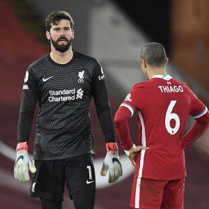 Alisson och Thiago tittar på varandra.