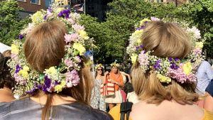 Fyra unga kvinnor med blomsterkrans på huvudet